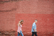 a couple walking in front of a red brick wall