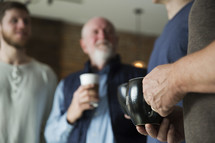 men's group with coffee mugs