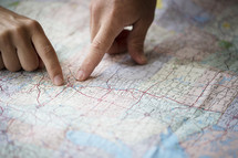 two people planning with fingers pointing to a map