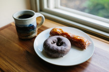 donut on a plate by a window