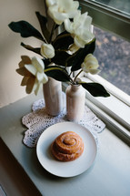 cinnamon bun on a plate on a table by a window