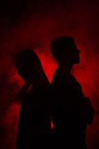 couple standing back to back in red glowing light