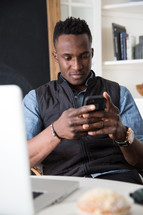 a man sitting in front of a laptop checking his cellphone