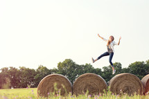 woman running and jumping on hay bales