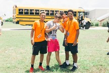 teenage boys in front of a school bus
