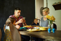 a father with a cellphone at the dinner table