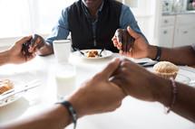 African American men holding hands in prayer