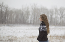 a young woman in a sweater standing in the snow