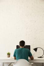 man working at his desk at a computer