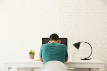 stressed man working at his desk at a computer.