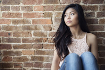 A pretty young woman sitting against a brick wall.