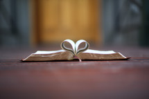 pages of a Bible folded into the shape of a heart in a doorway