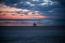 silhouette of a man on a bike on a beach at sunset