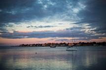 Boats sailing in the harbor at dusk.