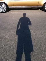 Boy's shadow on pavement in front of gold car.