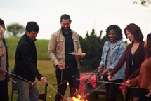 cooking hotdogs over a fire in fall