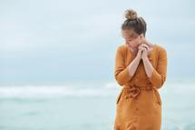 a woman standing on a beach praying