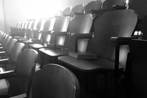 rows of seats in a theater with hymnals