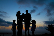silhouettes of a family at sunset