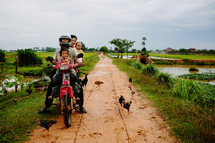 family on a dirt bike on a dirt road and chickens