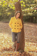 smiling young woman standing outdoors in fall