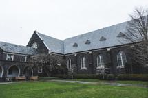 A stone church with a green lawn.