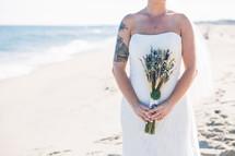 a bride on a beach holding a bouquet