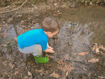 toddler boy in rain boots splashing in a puddle