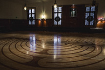 A large empty room with a circular patterned floor.