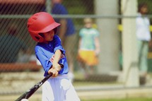 A young boy in little league swings and hits a baseball