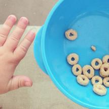 a toddler boy eating Cheerios