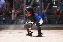 A young boy playing catcher at a little league baseball game