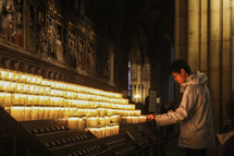 a man lighting a prayer candle in a cathedral