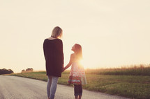 a mother and daughter standing holding hands talking outdoors
