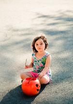 a girl child holding a jack-o-lantern