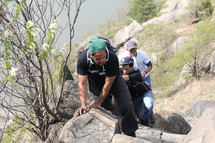 men climbing up a rocky terrain