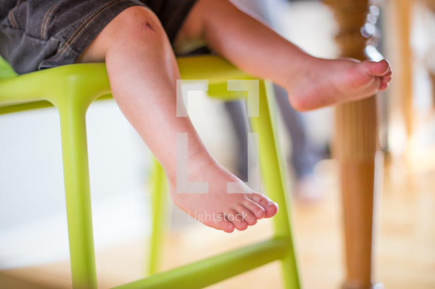 A toddler's legs hanging from a high chair.