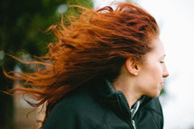 woman with red curly hair blowing in the wind