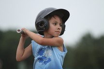 Boy set to swing a bat playing t-ball