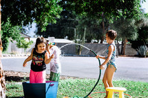 children playing with water outdoors on a hot summer day