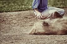 A young boy sliding into a base in a baseball game