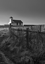 fence line and a white church on a beach