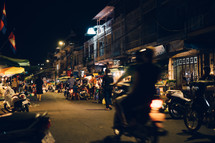 motorcycles entering a street market in Cambodia