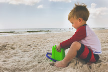 boy playing in the sand at the beach