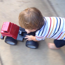 a toddler boy pushing a toy truck