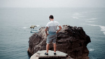 a man standing on a rock jetty