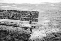 a weathered park bench along a shore