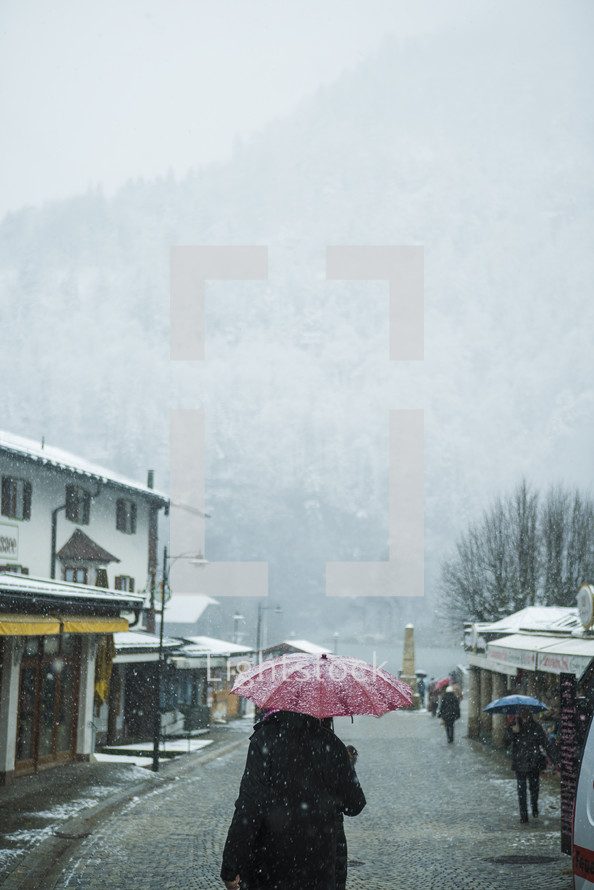 a woman walking carrying an umbrella in the snow