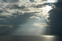Sun beaming through clouds on ocean. The Heavens declare the glory of God!
