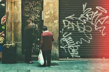 elderly women talking on a sidewalk in front of graffiti